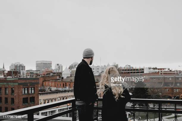 young couple looking out over a city - nordamerika stock-fotos und bilder
