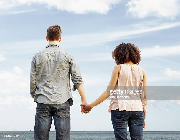 young couple looking out to sea, holding hands. - holding hands stock pictures, royalty-free photos & images