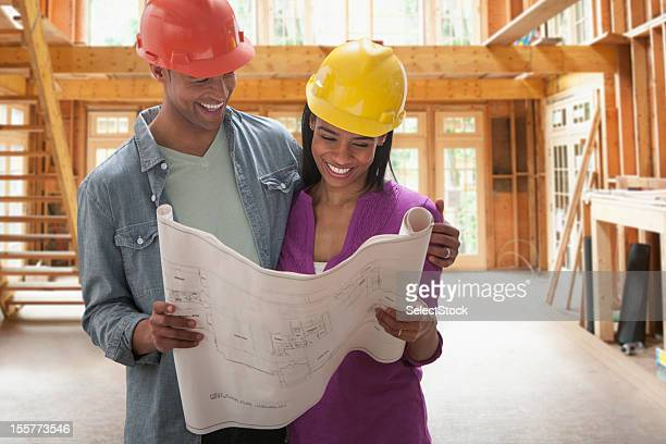 Young couple looking over blueprints to new home