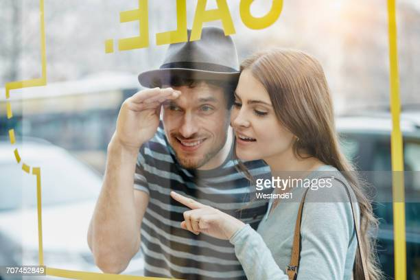 Young couple looking through window of a coffee shop