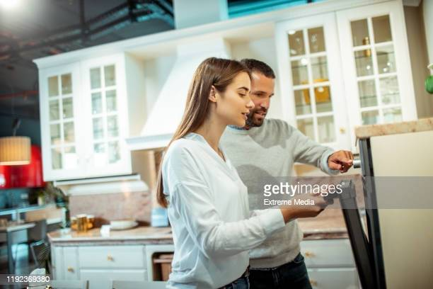 young couple looking to buy a new electric stove in a kitchen appliances shop - kitchenware shop stock pictures, royalty-free photos & images