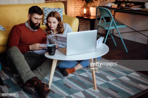 young couple looking trough mail expecting new orders - savings stock pictures, royalty-free photos & images