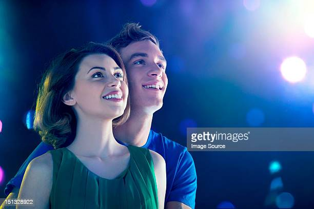young couple looking up at lights - awe stock pictures, royalty-free photos & images