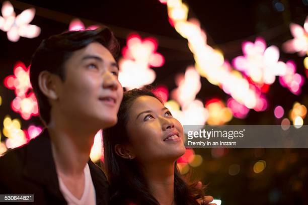 Young couple looking up at lights