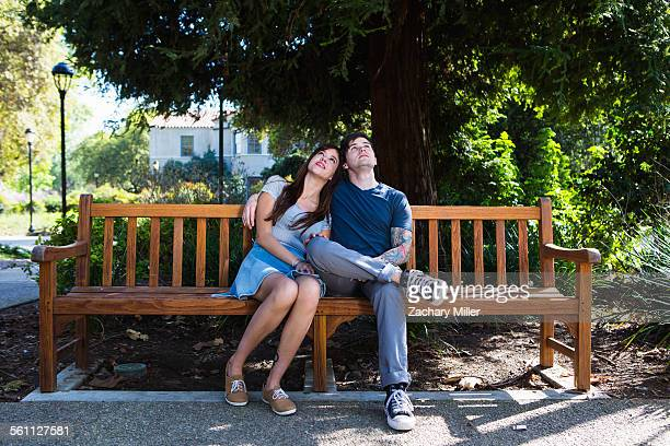 young couple looking up from park bench - bench stock pictures, royalty-free photos & images