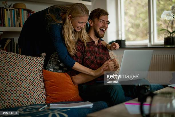 Young couple looking using laptop