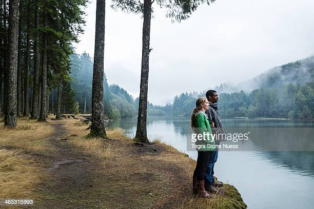 Young couple looks out over a misty lake.