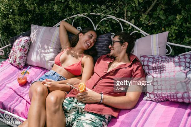 young couple lounging in the sun on an outdoor sofa - hot couple photos et images de collection