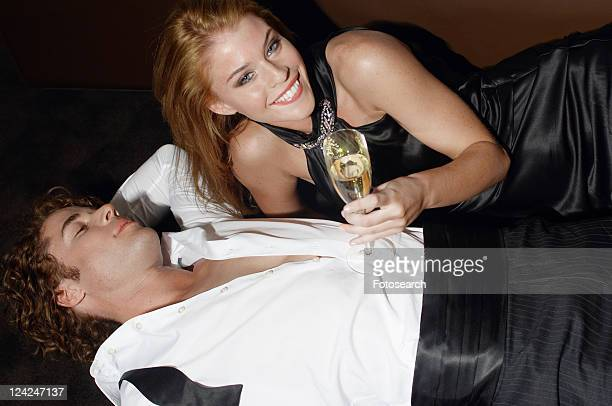 Young couple lying and celebrating with champagne