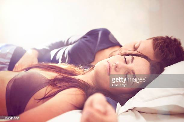 young couple lying asleep in bed, close-up - romantic young couple sleeping in bed stock photos and pictures