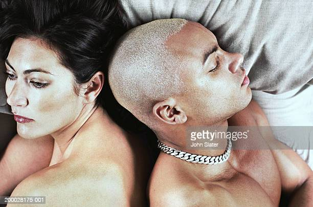 Young couple lying back to back in bed, man sleeping, close-up