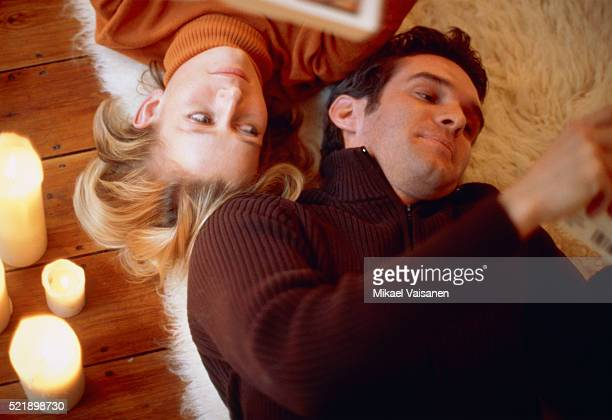 Young couple lying beside burning candles on the floor