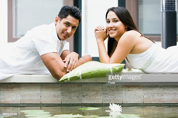 Young couple lying down next to pond