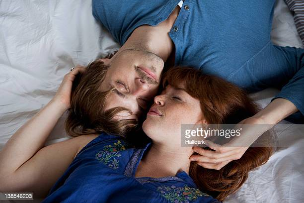 a young couple lying head to head on a bed, eyes closed - couple lit dormir amour photos et images de collection