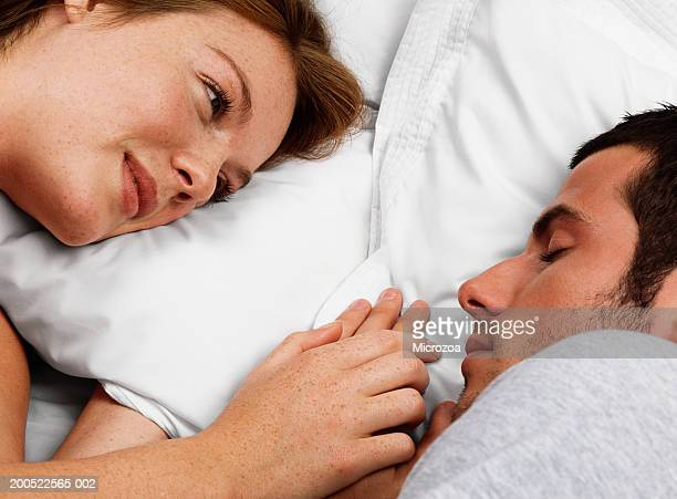 young couple lying in bed, man sleeping - microzoa stock pictures, royalty-free photos & images