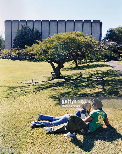 young couple lying in grass - blasius erlinger stock pictures, royalty-free photos & images