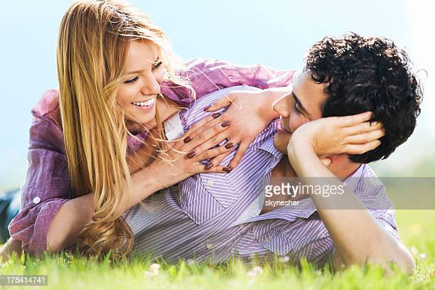 Young couple lying in park.