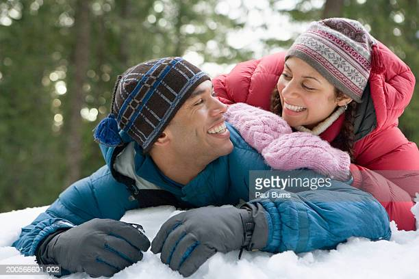 Young couple lying in snow, smiling