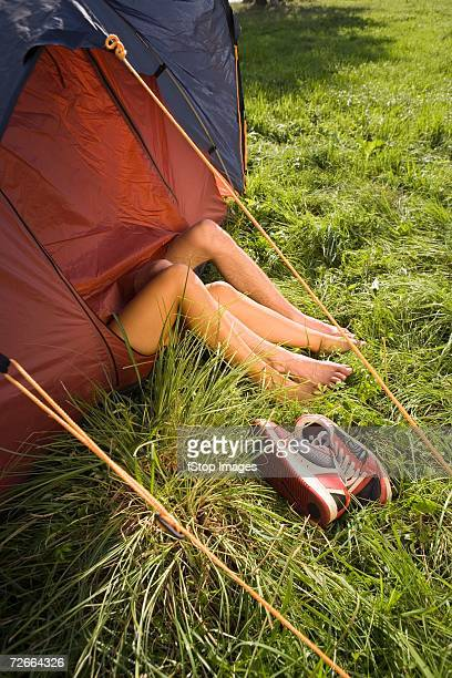 Young couple lying in tent with bare legs outside