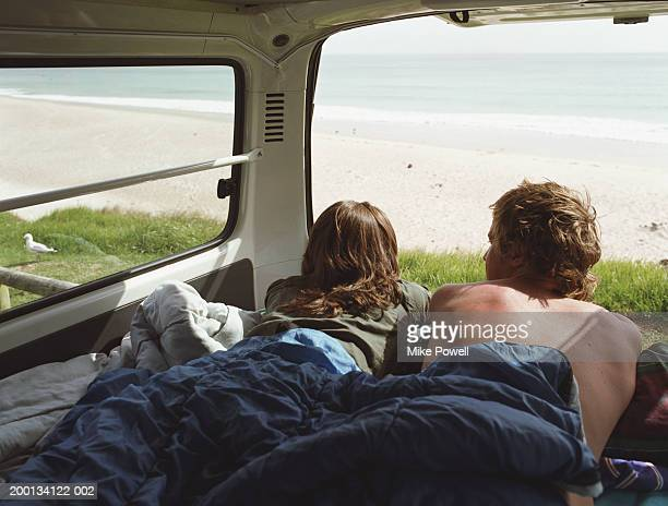 Young couple lying inside camper van parked near beach