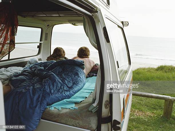 Young couple lying inside camper van parked near beach, rear view