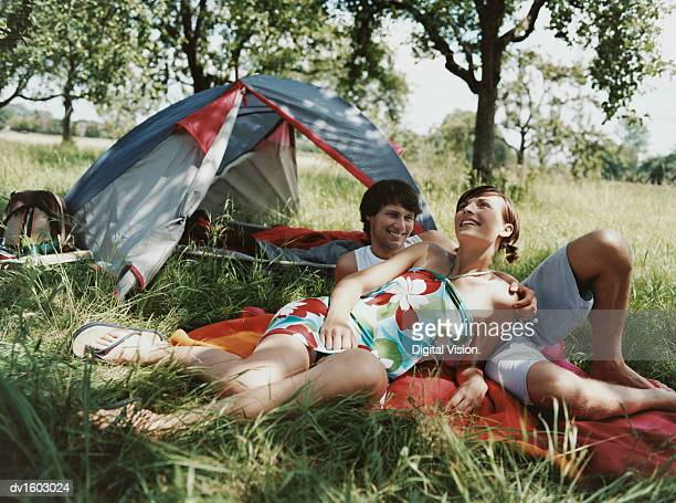 Young Couple Lying on a Blanket Next to Their Tent