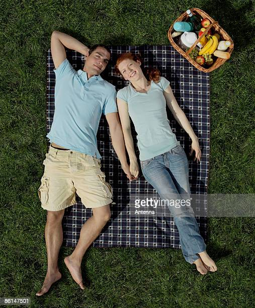A young couple lying on a blanket with a hamper