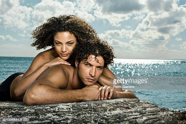 Young couple lying on beach, portrait