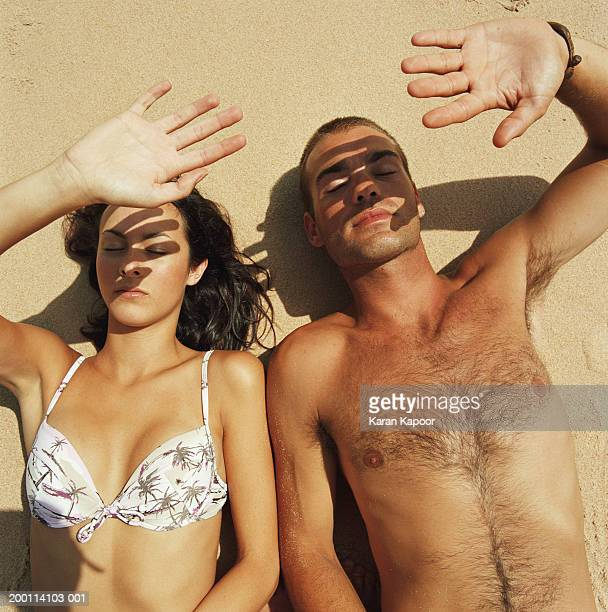 young couple lying on beach shielding faces from sun, elevated view - female hairy chest stock pictures, royalty-free photos & images