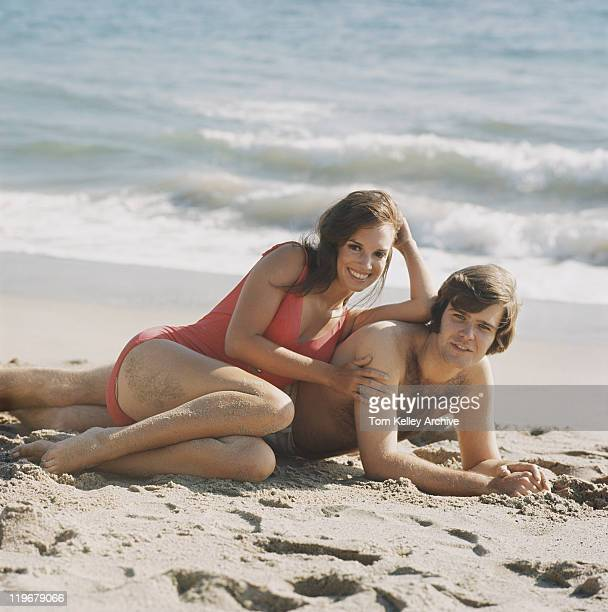 Young couple lying on beach, smiling, portrait