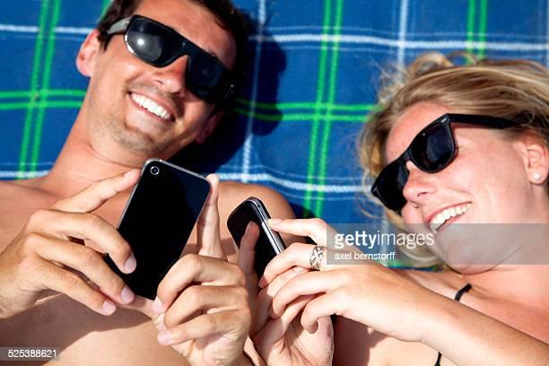 Young couple lying on beach towel using smartphones