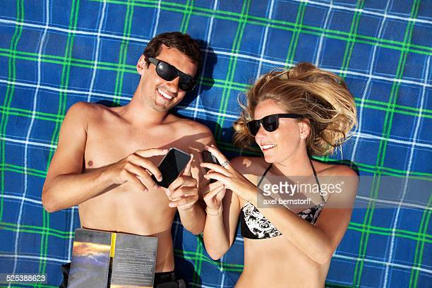 Young couple lying on beach towel using smartphones