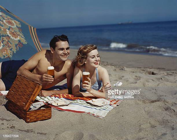 young couple lying on beach with beer, smiling - archiefbeelden stockfoto's en -beelden