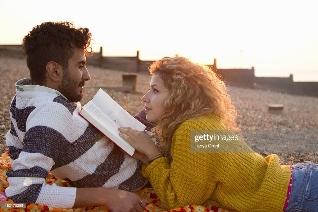 Young couple lying on beach, woman reading book : Stock Photo