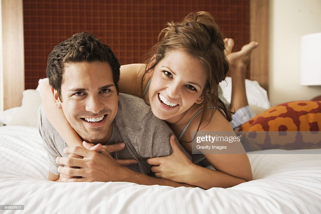 Young couple lying on bed, looking at camera. : Foto de stock