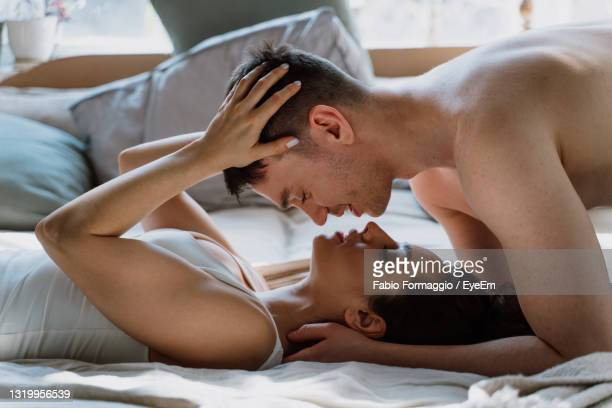 young couple lying on bed - satisfaction stock pictures, royalty-free photos & images