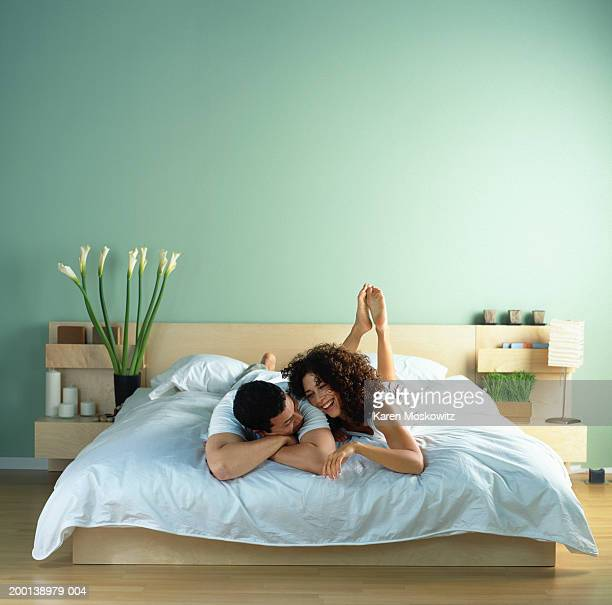 young couple lying on bed together - bed furniture stock pictures, royalty-free photos & images