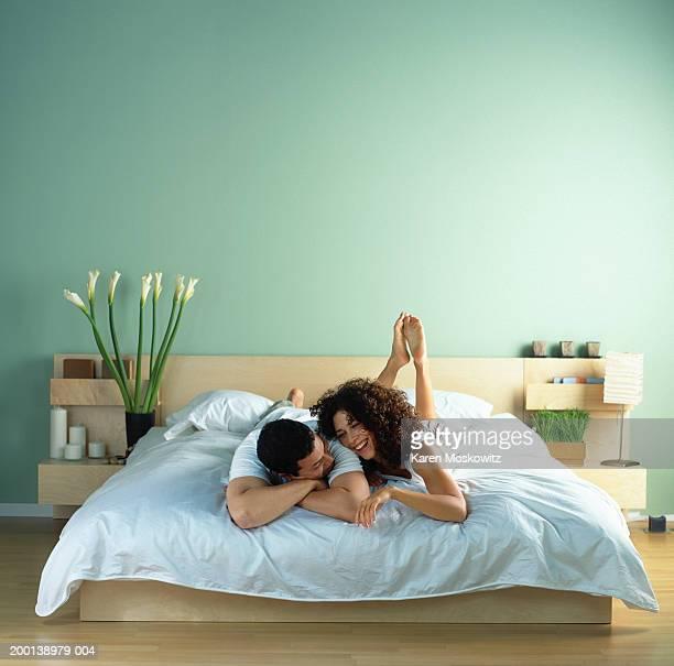 young couple lying on bed together - cama de casal - fotografias e filmes do acervo