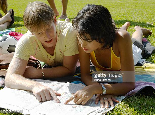 Young couple lying on blanket reading paper in park, close up