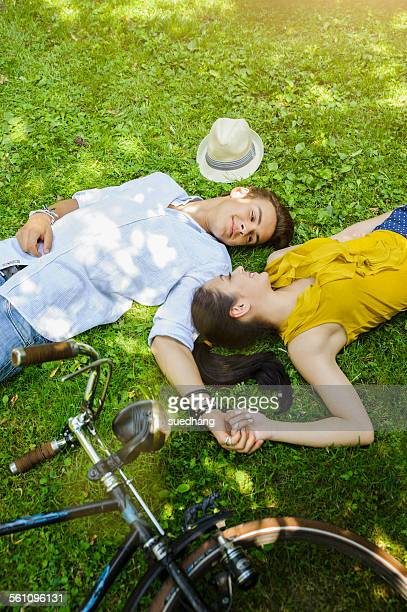 Young couple lying on grass holding hands