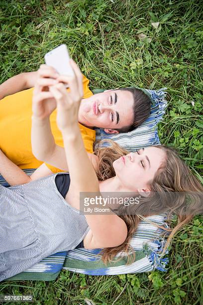 Young couple lying on grass in field, taking self portrait using smartphone
