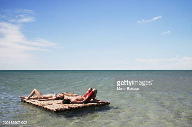 Young couple lying on raft at sea