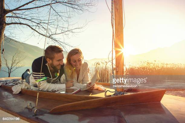 Young couple lying on sailboat above lake, relaxing
