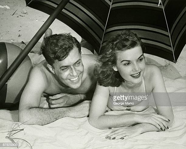 Young couple lying on sand under umbrella, smiling, (B&W)