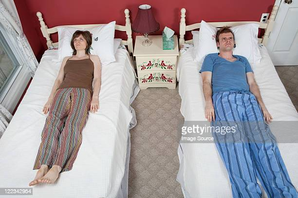 Young couple lying on single beds, ignoring each other