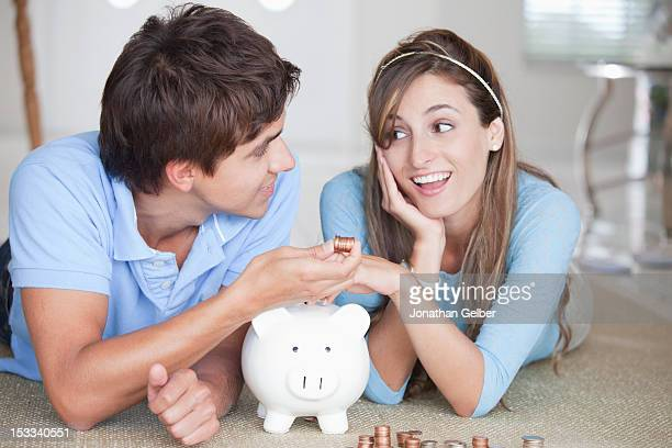 A young couple lying on the floor counting coins