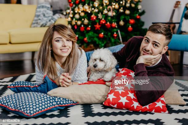 Young couple lying on the floor with the dog, decorated christmas tree in the background