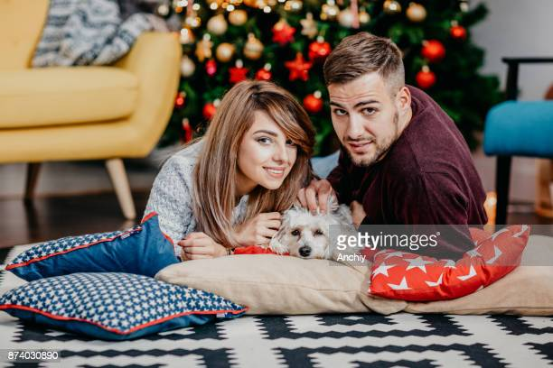 Young couple lying on the pillows with the dog, decorated Christmas tree in the background