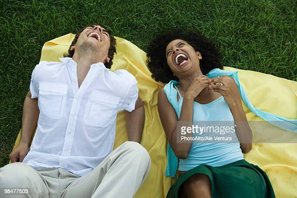 young couple lying together on blanket on grass laughing - head back stock pictures, royalty-free photos & images