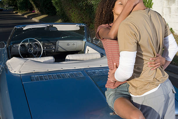Young Couple Macking on Car Trunk
